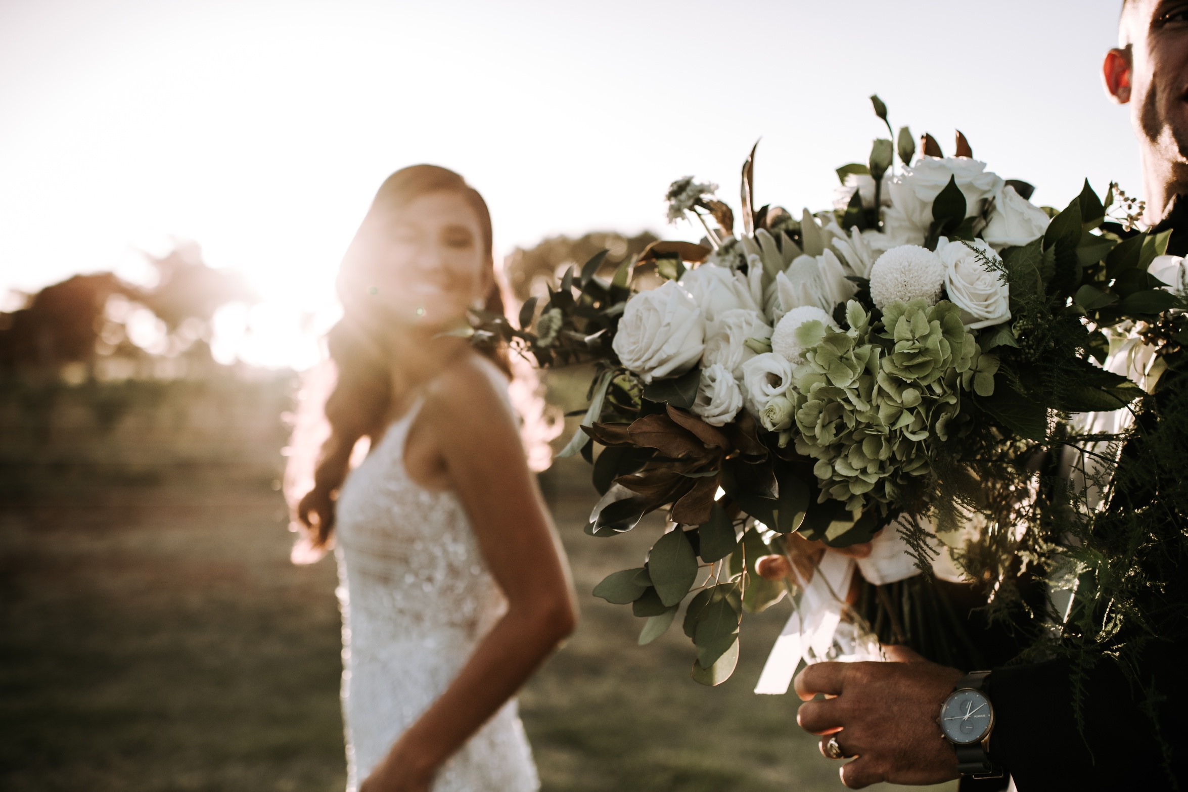 bride walking at sunset groom with bouquet